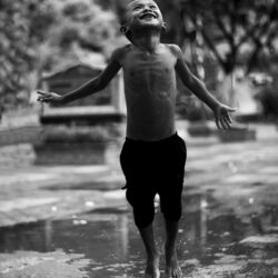 Little boy jumping in water